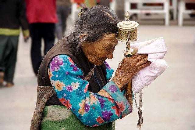אשה אוחזת בגלגל תפילה. בארקור. להסה. טיבט. באדיבות ויקיפדיה