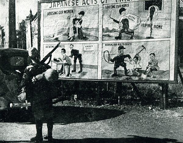 חייל יפני מתבונן בכרזה תעמולתית של האמריקאים. באדיבות ויקיפדיה