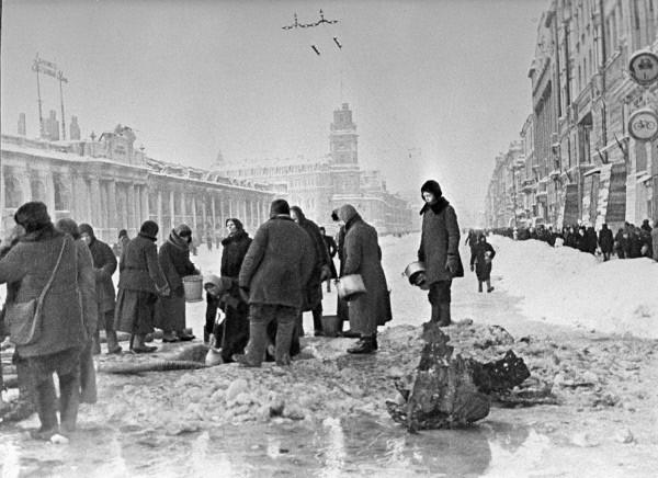 תושבי לנינגרד הנצורה אוספים מי שתייה משלולית מים שנקוו בחור באספלט בשדרות נבסקי לאחר הפצצה ארטילרית- דצמבר 1941. צילום: בוריס פ. קודויארוב