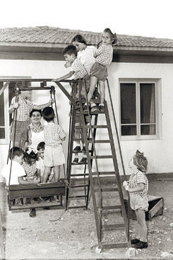 CHILDREN PLAYING IN FRONT OF CHILDREN'S HOUSE AT KIBBUTZ YEHIAM.