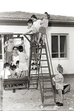 CHILDREN PLAYING IN FRONT OF CHILDREN'S HOUSE AT KIBBUTZ YEHIAM.
